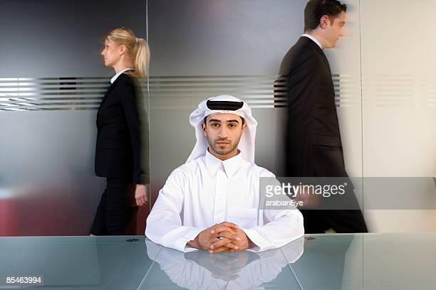 A Gulf Arab man sitting at conference table with two business colleagues walking behind him.