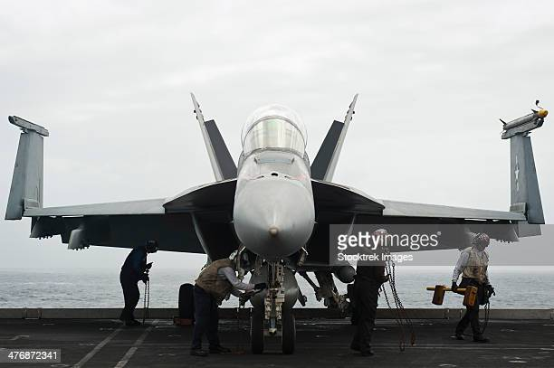 Gulf of Oman, August 28, 2013 - Sailors remove chocks and chains from an F/A-18F Super Hornet on the flight deck of the aircraft carrier USS Nimitz.