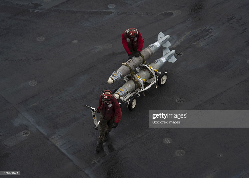 Gulf of Oman, June 13, 2013 - Marines move ordnance on the flight deck of the aircraft carrier USS Nimitz. : Stock Photo