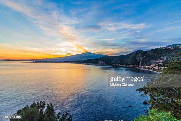 gulf of taormina with view of etna at sunset - mt etna stock pictures, royalty-free photos & images