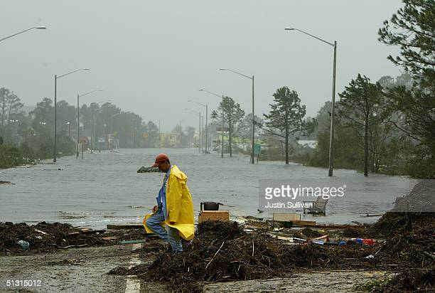 Gulf Shores city worker wlks by a flooded section of Highway 59 September 16, 2004 in Gulf Shores, Alabama. Workers begin to clean up after the...