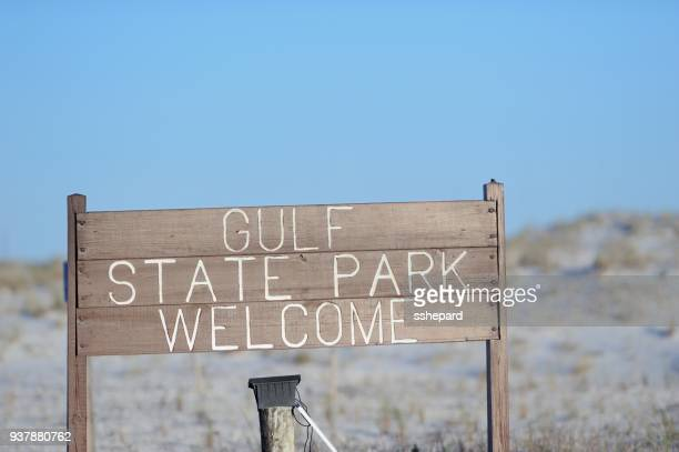 gulf state park welcome sign on road near beach - gulf shores alabama stock pictures, royalty-free photos & images