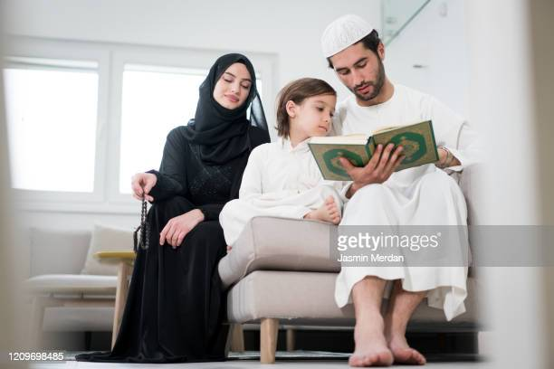 gulf young parents with little son reading koran in ramadan - koran stock pictures, royalty-free photos & images