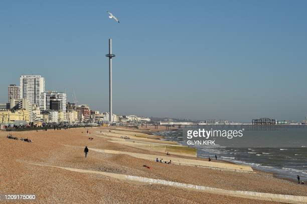 A gull flies above a neardeserted beach in Brighton on the south coast of England on April 5 as the warm weather tests the nationwide lockdown to...