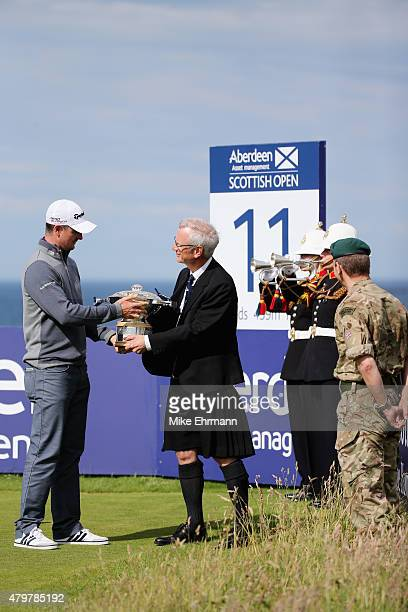 Gullane Golf Club Captain Robert Dick hands the Scottish Open trophy to defending Champion Justin Rose of England after it was delivered to Robert...