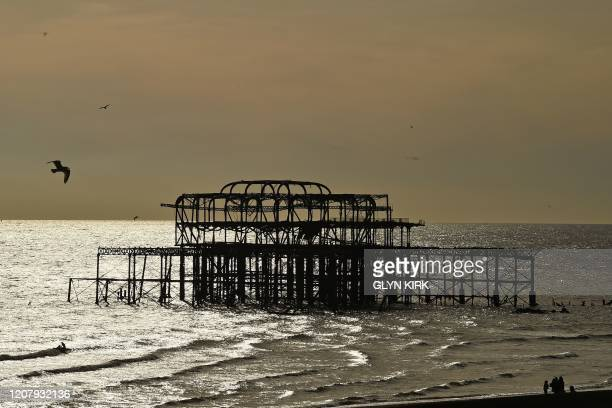 Gulls fly around the derelict West Pier in the early Spring sunshine in Brighton on the south coast of England on March 21 a day after the British...