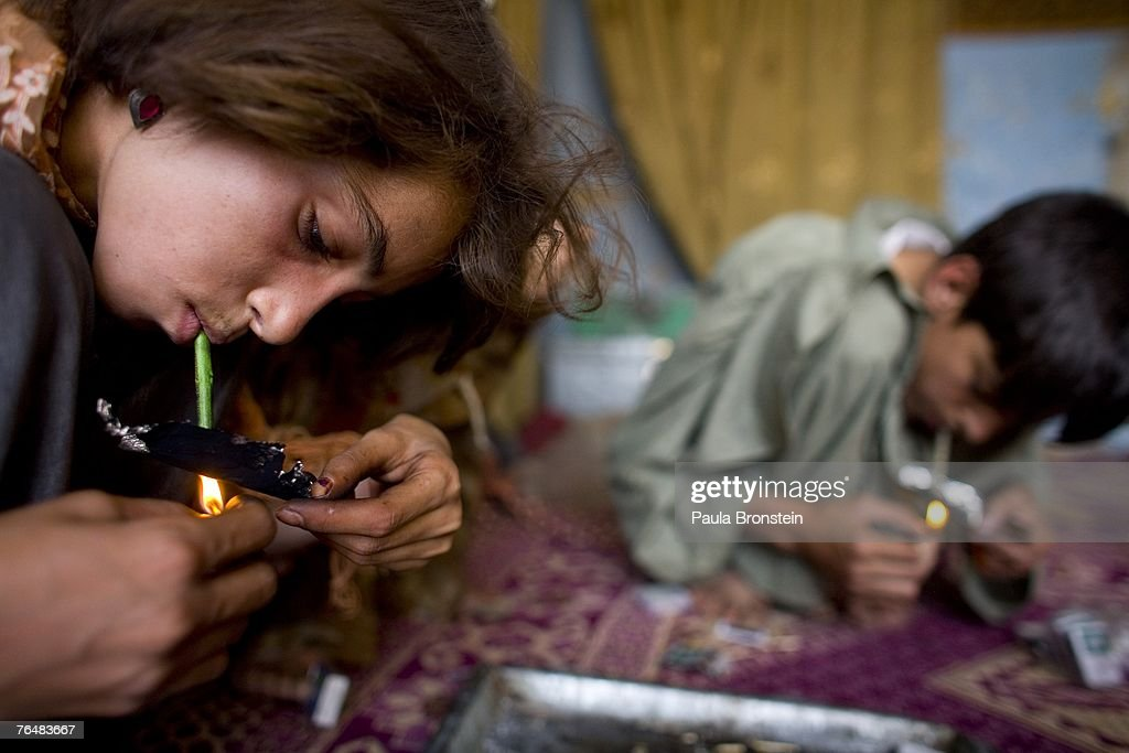 Gulparai, 12, (L) smokes heroin along side her mother Sabera and brother Zaher, 14, (R) August 27, 2007 in Kabul, Afghanistan. Gulparai's mother, Sabera, a widow, has been smoking for four years since she lost her husband. Her children, Gulparai and Zaher began smoking two years ago after watching their mother. The cost for daily use of the drug is around $3.00 USD or 150 in Afghani currency. Farmers in the Taliban-held areas of the south are also urged to grow opium. Although there are around 35,000 NATO troops in Afghanistan, the drug trade has increased, with Afghanistan producing 95 percent of the world's poppies. According to the UN Office on Drugs and Crime (UNODC), the opium production in 2006 increased 57 percent from 2005, with an additional 15% jump in 2007 despite a $600 million counter narcotics effort by the U.S.