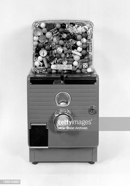 A gumball machine that dispenses gumballs and charms circa 1955