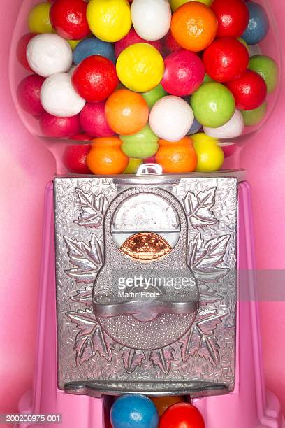 Gumball machine with one pence coin in slot, close-up