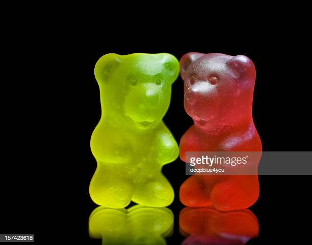 gummy bear couple close up isolated on black - gummi bears stock photos and pictures