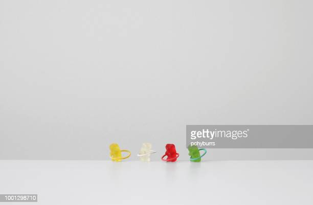 gummy bears exercising with plastic hoops - gummi bears stock photos and pictures