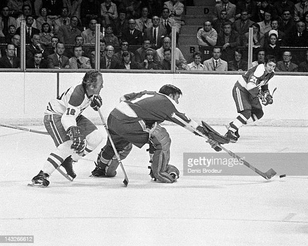 Gump Worsley of the Minnesota North Stars pushes the puck away from Henri Richard of the Montreal Canadiens Circa 1970 at the Montreal Forum in...