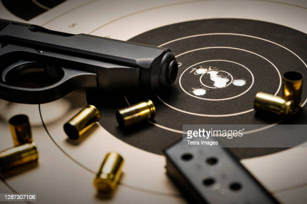 gun and ammo on target - weaponry stock pictures, royalty-free photos & images