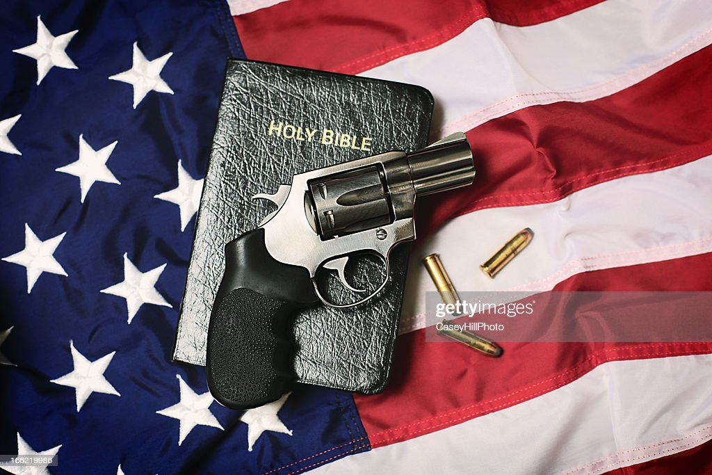 Gun and Bible on American Flag : Stock Photo