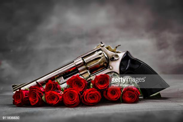 gun and roses - trigger stock pictures, royalty-free photos & images
