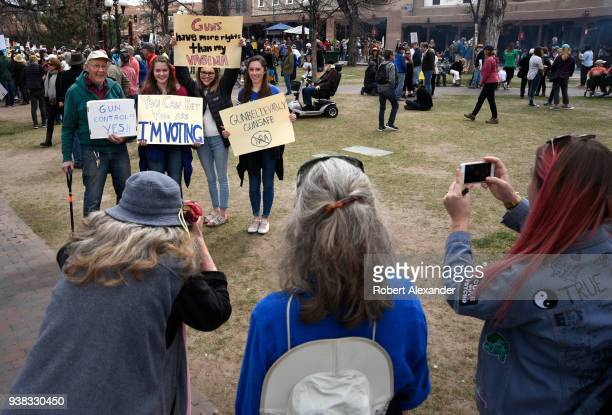 Gun control advocates hold signs referring to gun violence in America during a 'March For Our Lives' rally in Santa Fe New Mexico The rally and march...