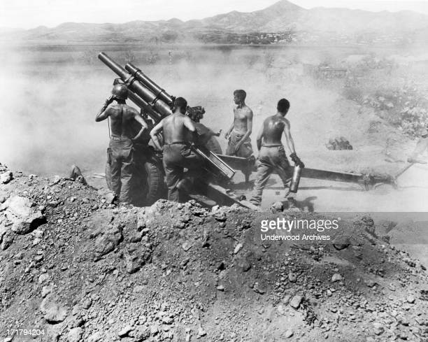 A gun crew of the 25th Infantry Division fire a 105mm howitzer on North Korean positions Uirson South Korea August 17 1950