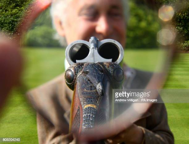 Gun Engraver Malcolm Appleby holds an unusual 12bore 'Crocodile' gun by David McKay Brown Malcolm engraved the gun to look like a crocodile and it is...