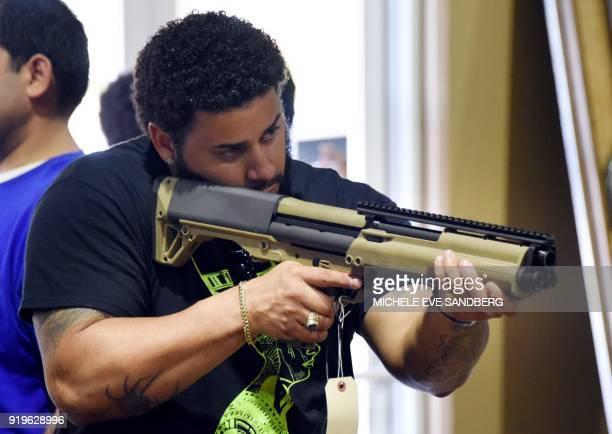 A gun enthusiast checks a weapon at the South Florida Gun Show at Dade County Youth Fairgrounds in Miami Florida on February 17 2018 The gun show...