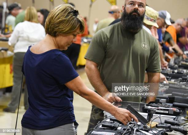 A gun enthusiast holds a weapon during the South Florida Gun Show at Dade County Youth Fairgrounds in Miami Florida on February 17 2018 The gun show...