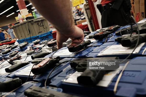Gun enthusiasts look at AR15 assault rifles at a gun show where thousands of different weapons are displayed for sale on July 10 2016 in Fort Worth...