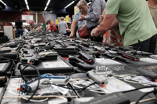 Gun enthusiasts look at AR-15 assault rifles at a gun show where thousands of different weapons are displayed for sale on July 10, 2016 in Fort...