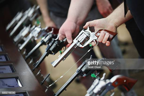 Gun enthusiasts look over Ruger pistols at the NRA Annual Meetings Exhibits on May 21 2016 in Louisville Kentucky About 80000 visitors are expected...