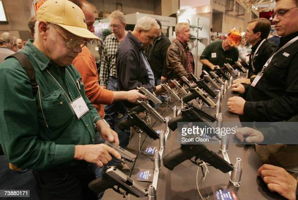 Gun enthusiasts look over Sigarms pistols during the 136th NRA Annual Meetings and Exhibits April 13 2007 in St Louis Missouri The fourday event is...