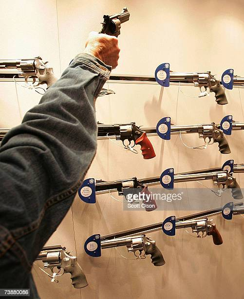 Gun enthusiasts look over Smith Wesson pistols during the 136th NRA Annual Meetings and Exhibits April 13 2007 in St Louis Missouri The fourday event...