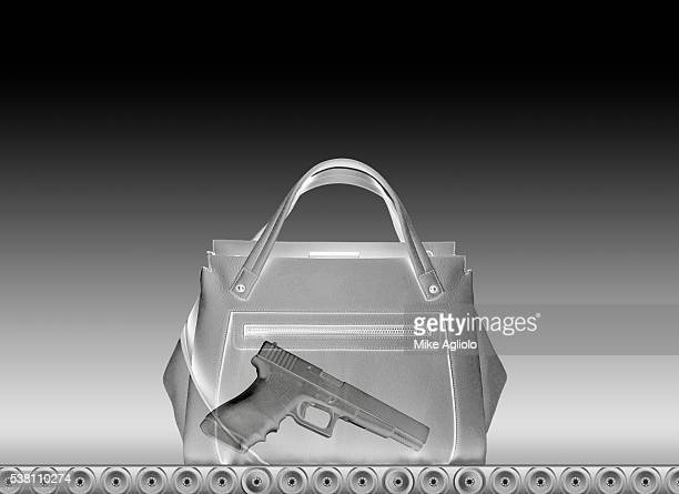 gun in a purse seen through airport security scanner - mike agliolo stock pictures, royalty-free photos & images