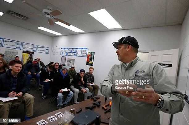 Gun instructor Mike Stilwell demonstrates an revolver as as he teaches a packed class to obtain the Utah concealed gun carry permit at Range Master...