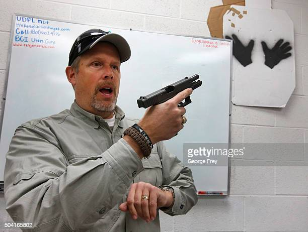 Gun instructor Mike Stilwell demonstrates an semi automatic hand gun as as he teaches a packed class to obtain the Utah concealed gun carry permit at...