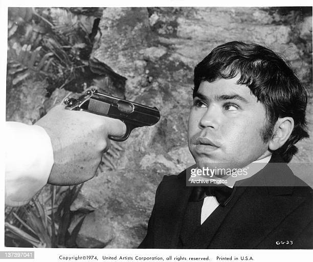 A gun is being pointed at Hervé Villechaize face in a scene from the film 'The Man With The Golden Gun' 1974