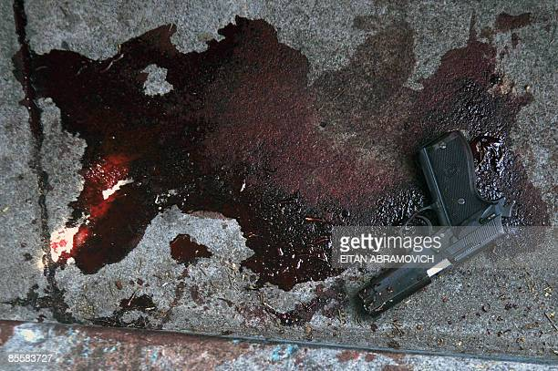 STORY A gun lies in a pool of blood close to the site where a passenger got killed in one of three attacks against public buses this morning in...