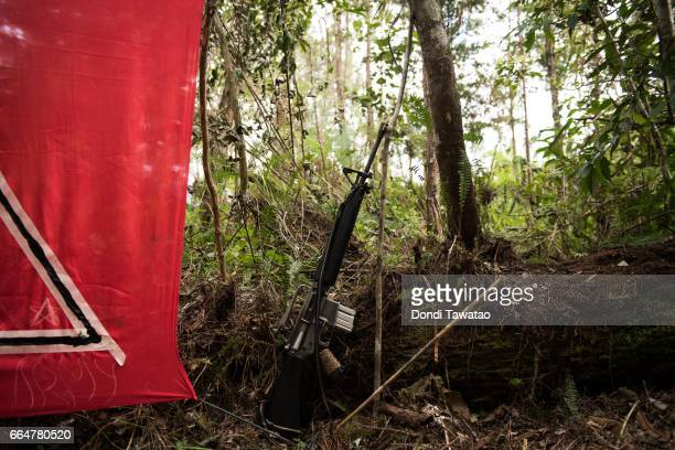 A gun rests beside a red flag at a temporary camp of the New People's Army on April 1 2017 in the remote hinterlands of Mountain Province Philippines...