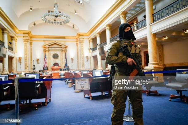 A gun rights activist carrying a semiautomatic firearm stands in the Senate Chamber of the Capitol Building on January 31 2020 in Frankfort Kentucky...
