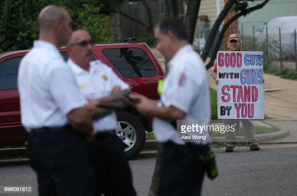 Gun rights activist Jeff Hulbert of Annapolis Maryland shows a poster as local residents gather outside The Anglican Catholic Church St Andrew St...