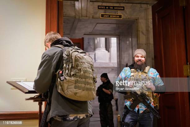 Gun rights activists carrying semiautomatic firearms sign the visitors log in Governor Andy Beshears Office at the Capitol Building on January 31...