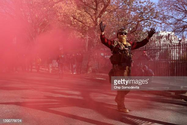 A gun rights advocate wearing body armor and carrying firearms sets off a smoke bomb at the conclusion of a rally organized by The Virginia Citizens...