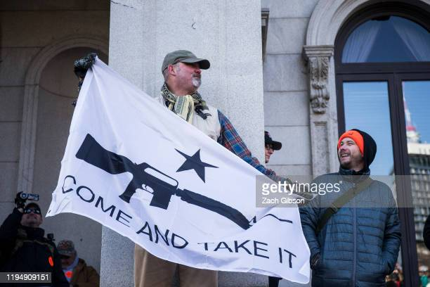 Gun rights advocates hold a flag during a rally organized by The Virginia Citizens Defense League on Capitol Square near the state capitol building...