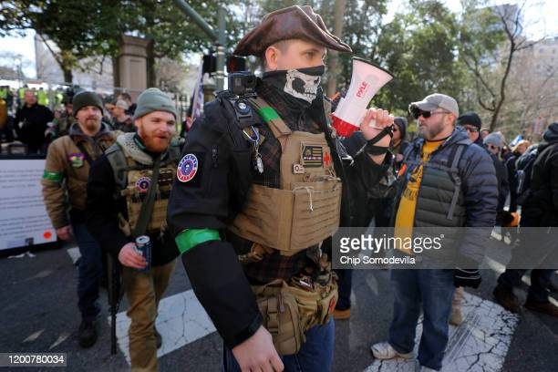 A gun rights advocates wearing body armor and carrying firearms leave a rally organized by The Virginia Citizens Defense League near the State...