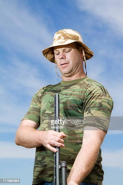 gun safety: careless man looking into the barrel of rifle - idiots stock pictures, royalty-free photos & images