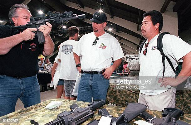 Gun salesman Steve Miller demonstrates a semi-automatic weapon to potential customers at the 31st Annual Great Western gun show 29 October 1999 in...