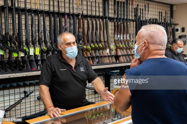 Gun shop employee wearing a protective face mask shows guns to customers at SP Firearms Unlimited as the city continues Phase 4 of re-opening...