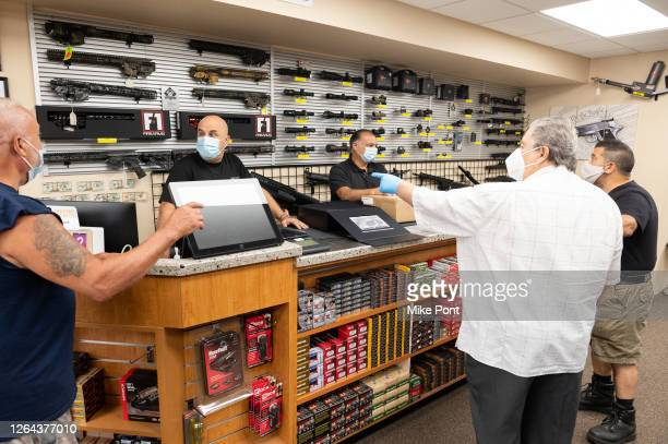 Gun shop employees and customers wearing protective face masks at SP Firearms Unlimited as the city continues Phase 4 of re-opening following...