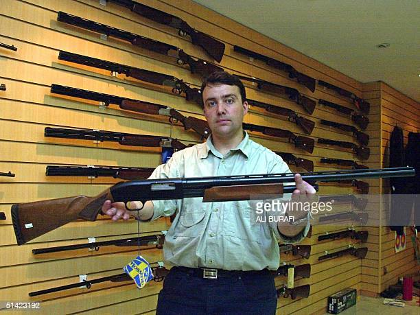Gun shop manager Julio Caroniholds holds one of the stores more popular item a 12 caliber rifle 24 January 2003 in Buenos Aires Argentina The stores...