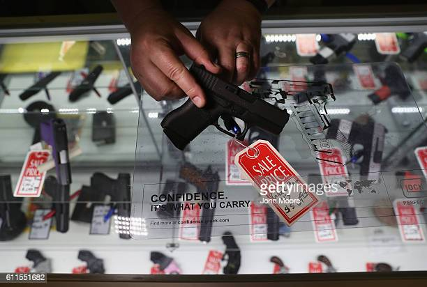 Gun shop owner Jeff Binkley displays a Glock 9mm pistol at Sarge's Sidearms on September 29 2016 in Benson Arizona He said he redesigned and renamed...