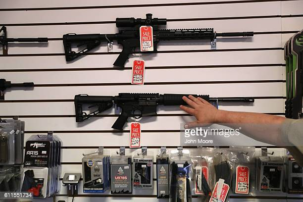 "Gun shop owner Jeff Binkley displays AR-15 ""Sport"" rifles at Sarge's Sidearms on September 29, 2016 in Benson, Arizona. He said he redesigned and..."