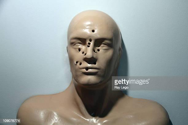 gun shots in face of human mold. - agujero de bala fotografías e imágenes de stock