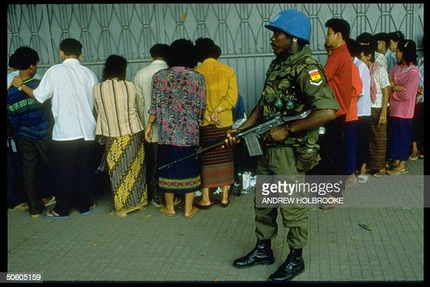 Gun wielding UN soldier keeping watch over line of voters truckedin to mobile polls during UNmonitored elections